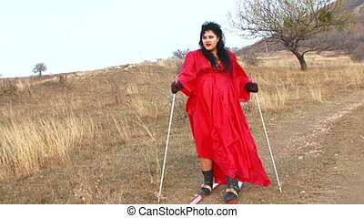 Trekking on skis on the savannah - A girl dressed in red...