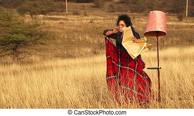 Girl smokes a cigar - The girl sits in the middle of savanna...