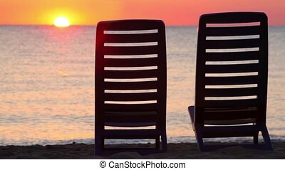 Seascape at evening sunset shown behind two deckchairs