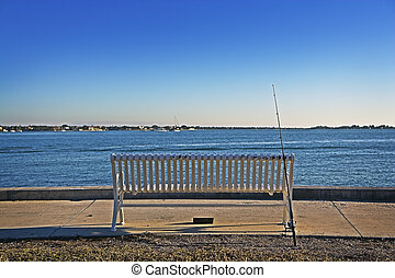 Fishing Pole & Bench - A fishing pole leans against a metal...