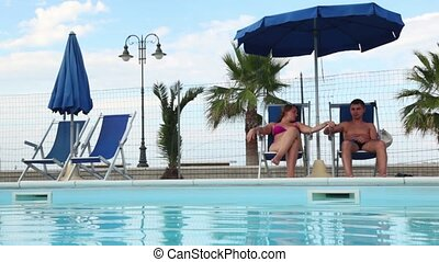 Couple sitting in deckchairs in front of the pool