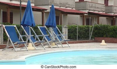 Several deckchairs facing the pool against the backdrop of an hotel