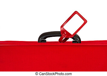 Red suitcase with blank identification tag over white...