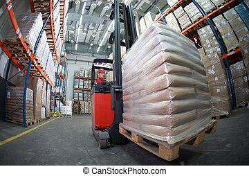 Working at the storehouse - Forklift operator in red uniform...