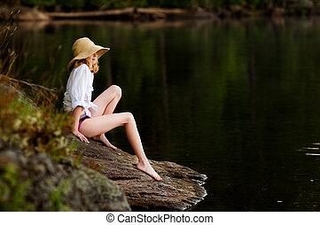 girl sitting on a rock by a lake