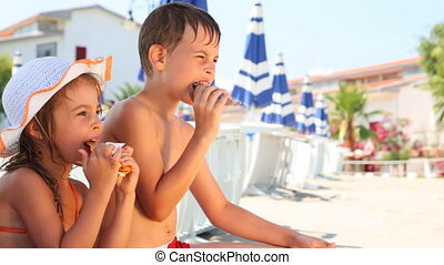 Boy and girl eat ice cream on beach, then he licks his hand...