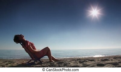 Woman leaned back on deckchair and tans without movement, on...