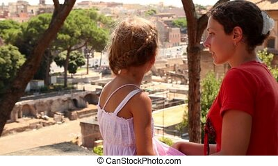 Mom tells her daughter about something, ruins of Forum of...