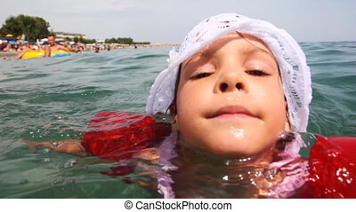 Little girl in inflatable arm ruffles swims at sea