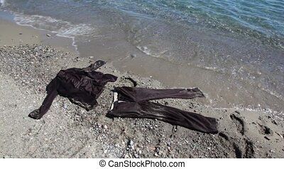 Brown suit lay on sand near sea water, waves wetting sleeve...