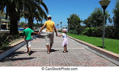 Man with daughter and son go on walkway to hotel - Man with...