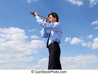 young business man looks through a telescope - young...