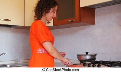 Girl at kitchen interferes with spoon in saucepan on stove -...