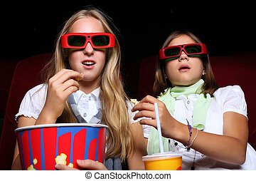Two young girls watching in cinema - Two young girls...