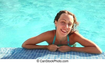 Woman laying in wavy pool water