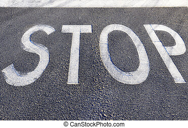 Stop sign - A stop sign painted on asfalt on a road