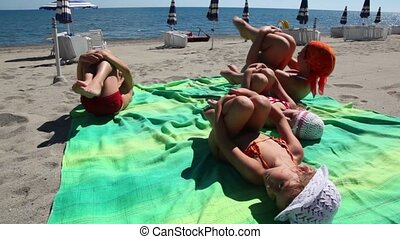 Woman and kids laying on beach hugging their knees