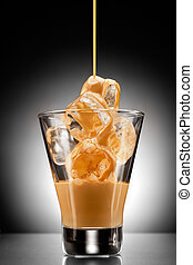 Irish spirit - Irish creme liqueur pouring into a glass full...