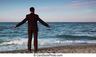 Man in suit standing on beach pebbles