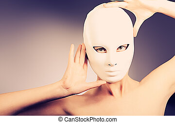 anonym - Shot of a woman in white mask over grey background.