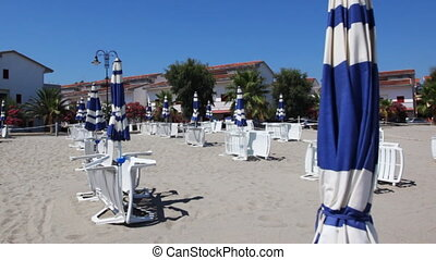 Beach near town with downcast umbrellas and sunbeds on their...