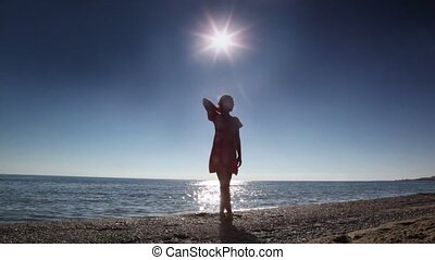 Woman standing on beach with her hand bent at the elbow...