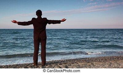 Man in suit standing on beach pebbles and watching seascape