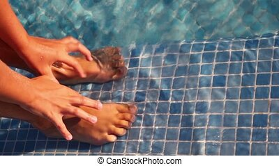 Two legs and two arms shown in pool water, hands splutter