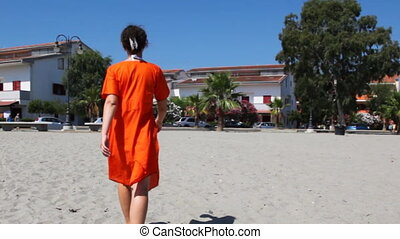 Pretty girl goes on sand to city - Pretty girl in orange...