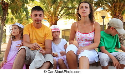 Family sits on bench among palm trees in summer sunny day...