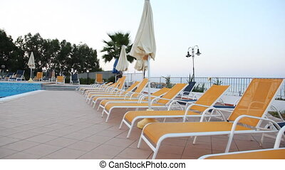 Beach beds and sunshades by pool, shooting moving camera