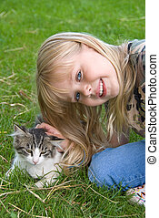 girl petting kitten - Little blond girl petting a tabby...