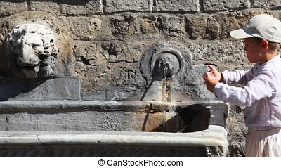 Boy stands and drinks water from old source on stone wall -...