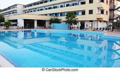 Hotel and swimming pool with clear blue water, shooting...
