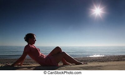 Woman sitting on beach sand at sunny day, sea behind