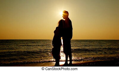 Girl and boy stand on seashore, she gently presses back to him, silhouettes at sunset, part3