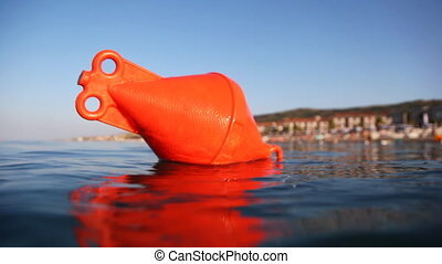 Buoy floats into sea - Orange buoy floats into sea, camera...