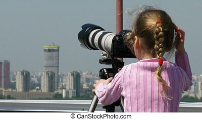 Little girl on top of the roof look trough big photo lenses