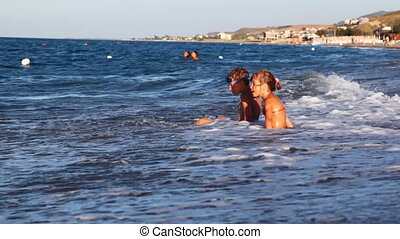 Little girl and boy play with waves at edge of sea in bright...