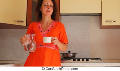 Girl at kitchen pours out of carafe water in mug