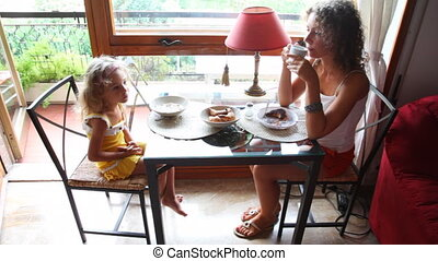 Mother and daughter eat breakfast sitting at table