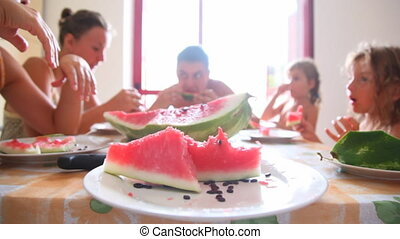 Sliced watermelon on plate and family around table eat it -...