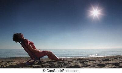 Woman leaned back on deckchair and tans, on beach at sunny...