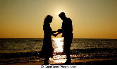 Boy and girl standing on beach, silhouettes at sunset, part2...