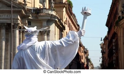 Mummer in white suit of the Statue of Liberty stands and...