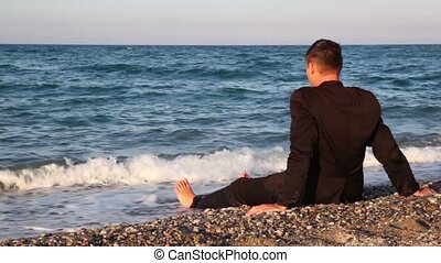 Man in suit sitting on beach pebbles