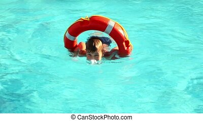 Boy swimming in the pool water - Boy in red lifebuoy...