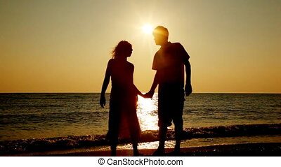 Girl and boy stand touching noses on seashore, silhouettes...