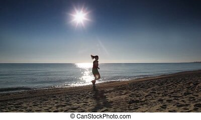 Young woman runs along beach near sea water at summer sunny...
