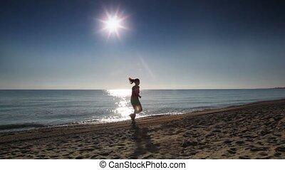 Young woman runs along beach near sea water at summer sunny...